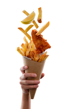 Falling fish and chips into a paper cone. Lemon for squeezing juice. Takeout food, traditional British cuisine. 写真素材