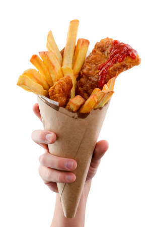 Hand is holding a paper cone full of appetizing fish and fries. Popular street food, lunch meal ideas.