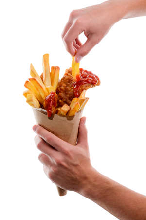 Eating fish and chips. Male hand is taking a French frie from paper cone wrapper. Takeout street food.