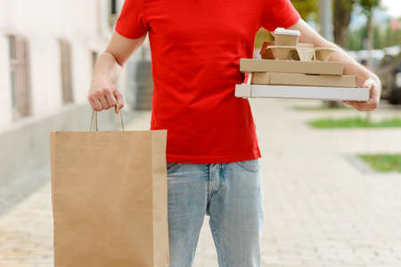 Man holding a paper bag and food boxes with pizza, coffee and burgers