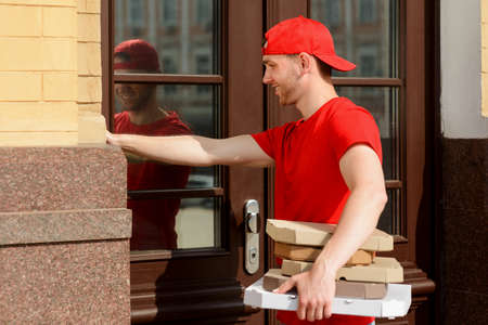 Man is ringing door bell and holding plenty of paper containers Imagens