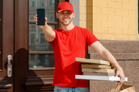 Delivery man showing a phone and holding several boxes of pizza