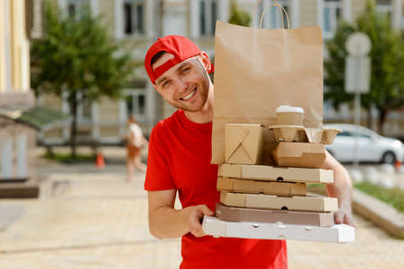 Handsome delivery man holding a big order in his hands Imagens