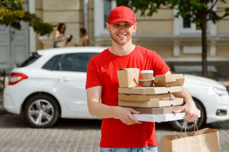 Delivery man loves his job. Cheerful young man carrying paper containers Imagens
