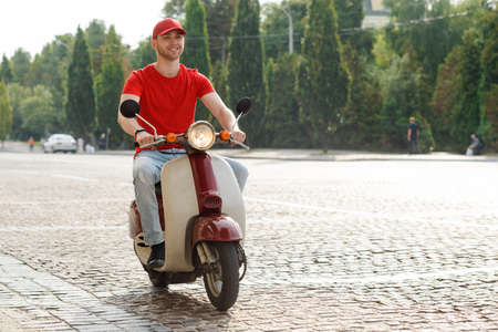 Man driving down a paved road on a motorcycle