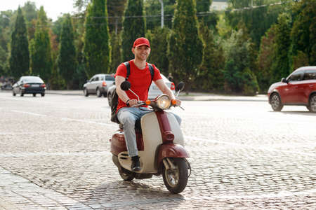 Handsome guy is driving a motorbike, delivery service