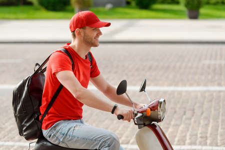 Young man is riding on a motorbike Imagens