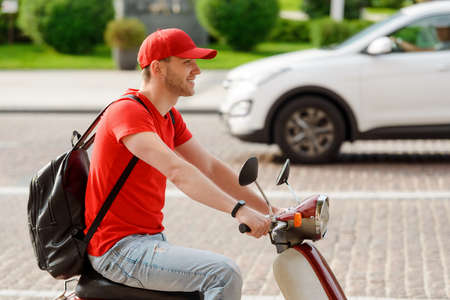 Guy is driving a scooter. Happy deliveryman