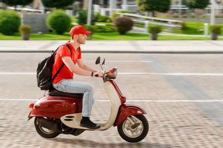Young guy working as deliveryman. Man is driving a scooter Imagens