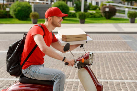 Happy guy is delivering pizza. Man drives a motorbike
