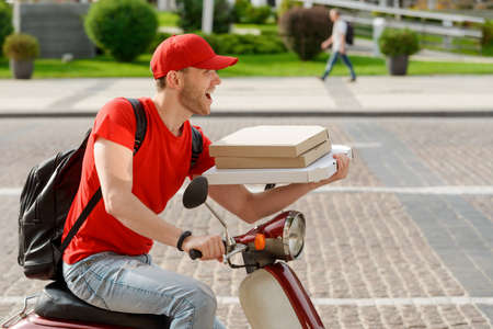Italian pizza delivery concept. Smiling courier delivering food