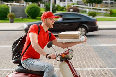 Young man is delivering pizza, driving on a scooter