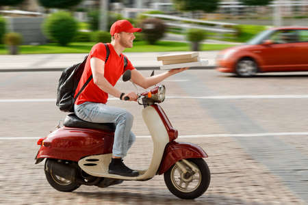 Deliveryman driving through the city on a motorbike Imagens