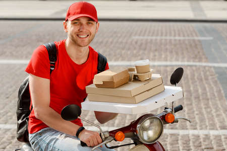 Portrait of a deliveryman. Smiling young guy is showing boxes of pizza
