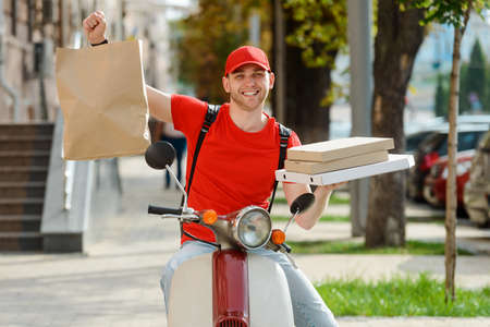 Deliveryman is showing food package, holding a parcel and boxes