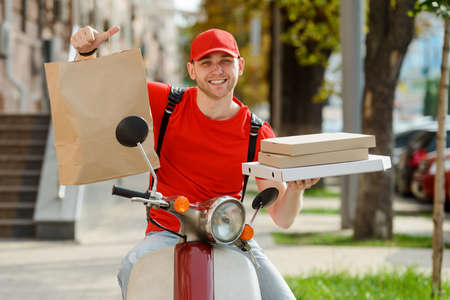 Portrait of a delivery man posing with paper pocket and pizza boxes Imagens
