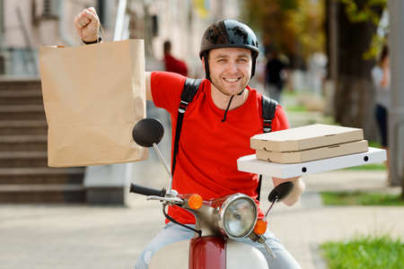 Food and products delivery. Happy worker holding paper parcel and pizza boxes Imagens