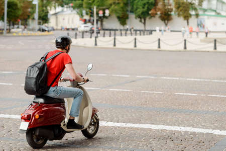 Man, with a backpack and helmet, is driving a scooter Imagens