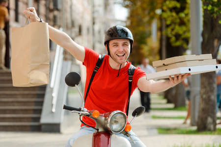 Guy working as delivery man, showing a paper parcel and boxes wide open arms