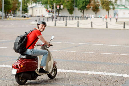 Delighted man, wearing a backpack and a helmet, driving a motorbike Imagens