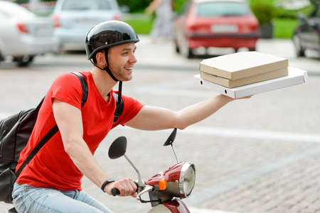 Man works for delivery service, driving a motorbike and carrying pizza boxes