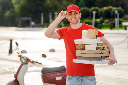 Portrait of a delivery man with food packages on city background Archivio Fotografico