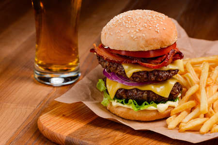 Double burger and French fries on wooden tray Imagens