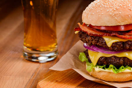 Double hamburger and beer on a wooden table, selective focus