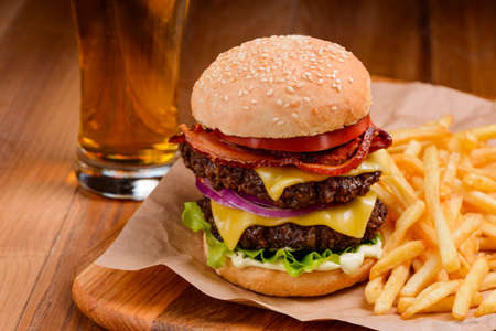 Big double cheeseburger served with handful of French fries and glass of beer