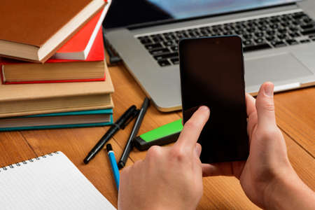 Man touching screen of a phone. Books, laptop and pens 스톡 콘텐츠