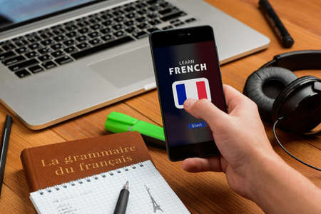 Man is learning French using a smart phone app Фото со стока