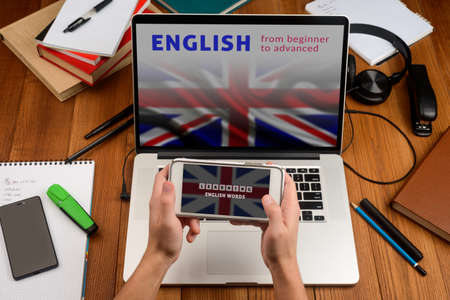 Learning English online. Man opened applications on his phone and laptop
