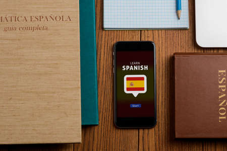 Learn Spanish app and textbooks on wooden table Фото со стока