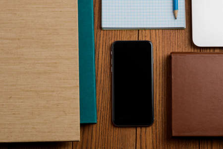 Phone beside books, laptop and office supplies on the wooden table