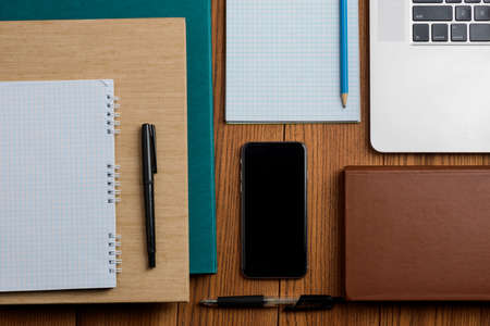 Books, phone, laptop and office supplies on wooden desktop