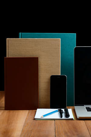 Electronic gadgets, books and stationery on wooden table