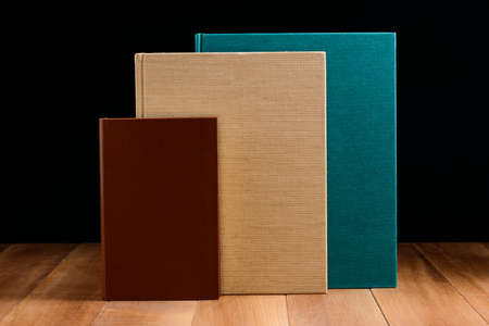 Group of three books on wooden surface