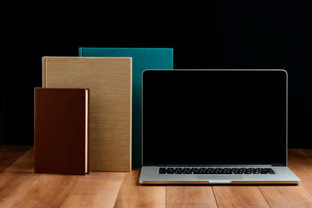 Hardcover books and laptop on wooden desktop