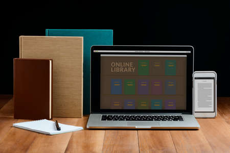 Books, laptop and mobile phone on wooden table
