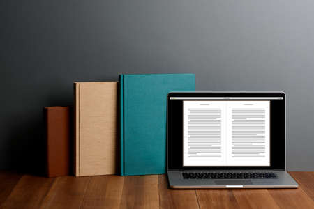 Books and laptop with E-reader app on desktop