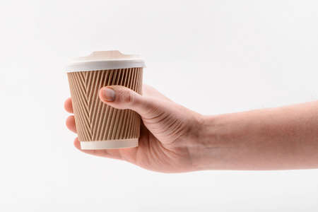Hand holding a corrugated paper cup on white background