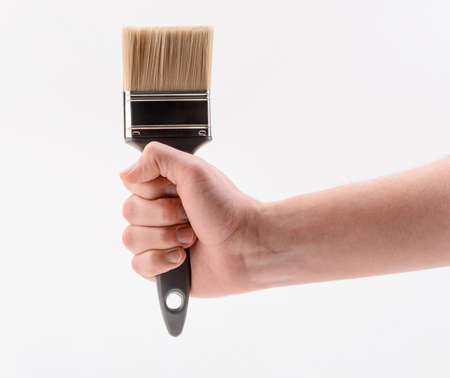 Hand holding firmly a paintbrush, isolated on white background