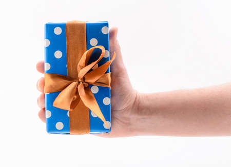 Hand holding a gift box, isolated on white