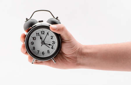 Hand holding a black alarm clock on white background