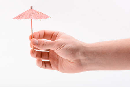 Hand holding a paper umbrella, isolated on white