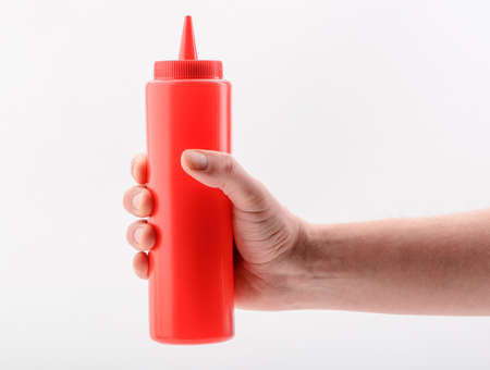 Hand holding a red squeeze bottle, isolated on white background Reklamní fotografie