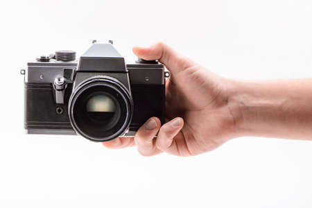 Hand holding a vintage camera, isolated on white background