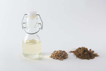 A bottle of hemp oil, seeds and a handful of flour on white background