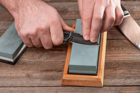 Man sharpens his knives with a whetstone on a rustic wooden tabl