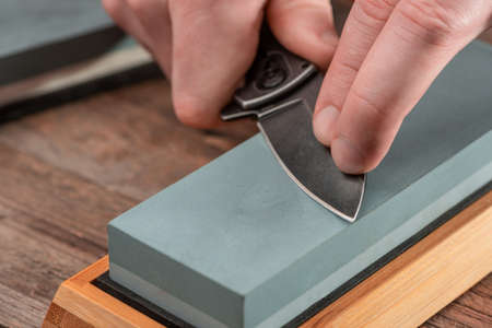 Man using a whetstone to sharpen his pocket knife